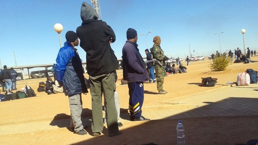 In this Jan. 16, 2013 photo secretly taken by a hostage, an Islamic militant, in camouflage uniform, rear right, stands near Algerian employees who were forced to leave their houses with their belongings at the Ain Amenas natural gas complex in Ain Amenas, Algeria.