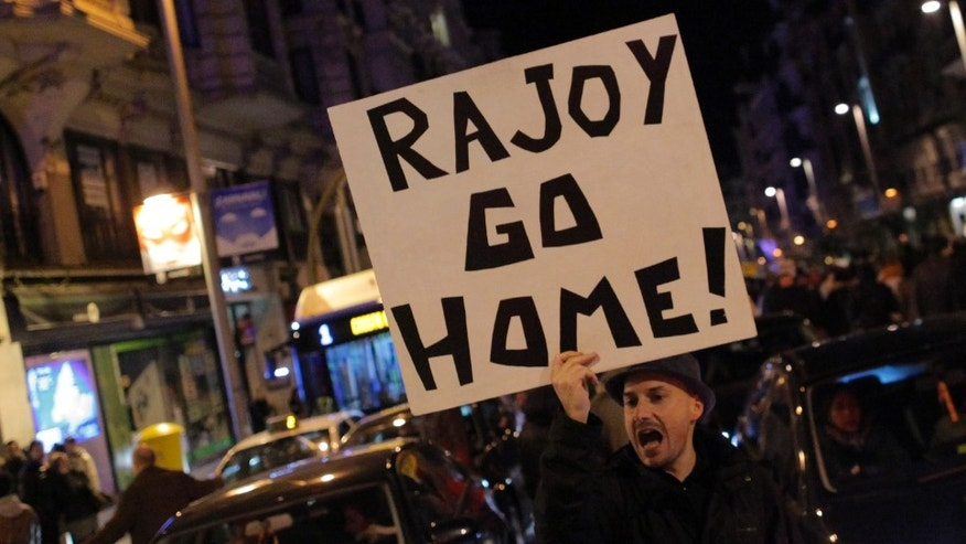 "Protestors shout slogans as they carry banners reading, ""Rajoy go home"" during a demonstration against corruption in Madrid, Spain, Saturday, Feb. 2, 2013.(AP Photo/Andres Kudacki)"