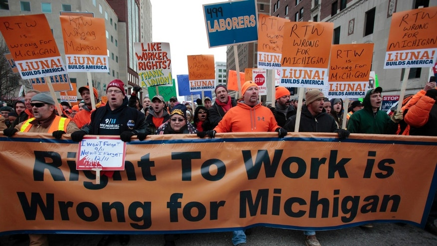 FILE: Dec. 11, 2012: Union members and supporters march to the Michigan State Capitol  to protest against right-to-work legislation, in Lansing, Mich.