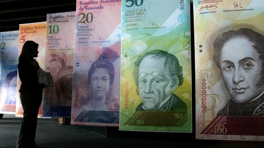 FILE - In this Oct. 24, 2007 file photo, a woman looks at oversized versions of the new Venezuelan currency, coined the 'Strong Bolivar' in Caracas, Venezuela. Venezuela's government announced Friday, Feb. 8, 2013, that it is devaluing the country's currency, a long-anticipated change expected to push up prices in the heavily import-reliant economy. Officials said the fixed exchange rate is changing from 4.30 bolivars to the dollar to 6.30 bolivars to the dollar. Venezuela's government has had strict currency exchange controls since 2003 and maintains a fixed, government-set exchange rate. (AP Photo/Howard Yanes, File)