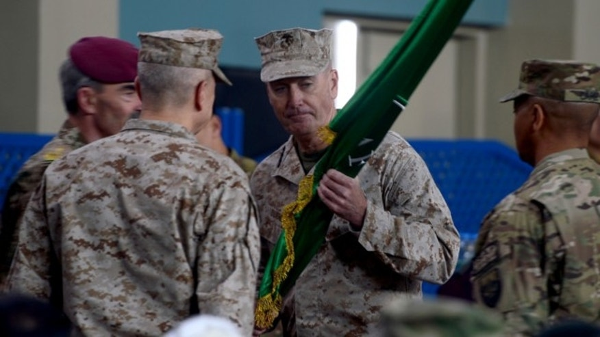Feb. 10, 2013: U.S. Marine Gen. Joseph F. Dunford, center, receives a flag from outgoing ISAF commander, U.S. Gen. John Allen, left facing away from camera, at the ISAF headquarters in Kabul, Afghanistan.