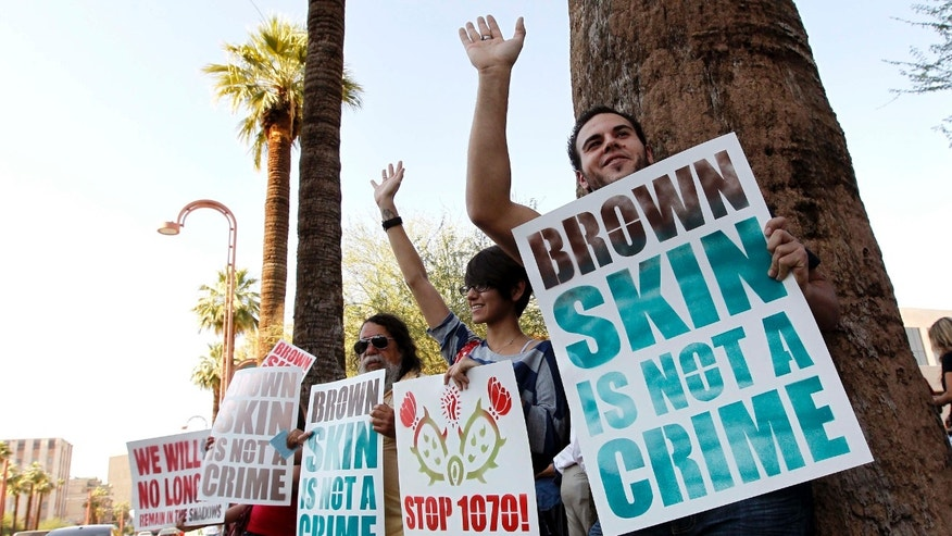 Laurent Taillefer, right, and Andrea Begay, second from right, both of Phoenix, wave at cars as they honk their horns driving by as the two join immigration rights protesters as they gather after the United States Supreme Court decision regarding Arizona's controversial immigration law, SB1070, at the local U.S. Immigration and Customs Enforcement offices Monday, June 25, 2012, in Phoenix. The Supreme Court struck down key provisions of Arizona's crackdown on immigrants Monday but said a much-debated portion on checking suspects' status could go forward. (AP Photo/Ross D. Franklin)