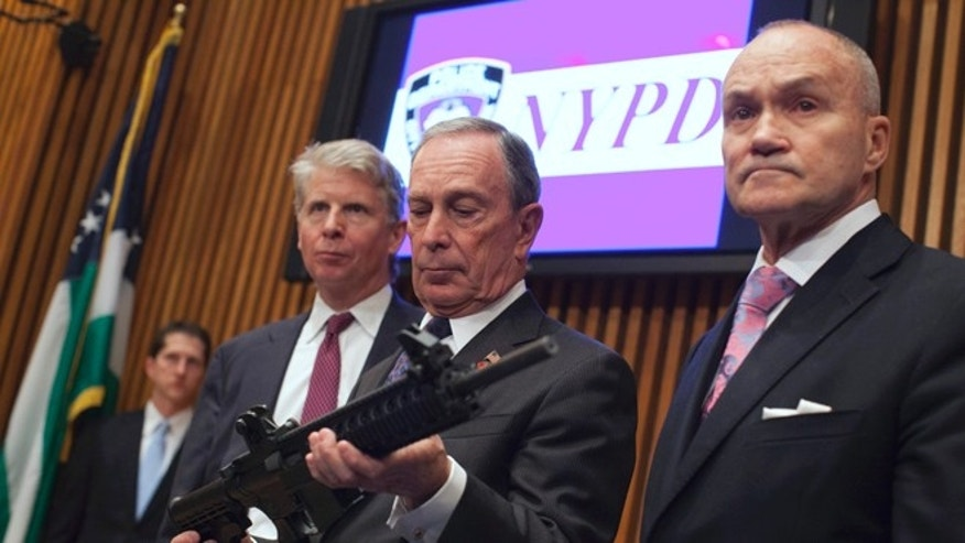 Oct. 12, 2012: Mayor Michael Bloomberg, center, examines a confiscated gun with Police Commissioner Ray Kelly, right, and District Attorney Cyrus Vance in New York. (Reuters)