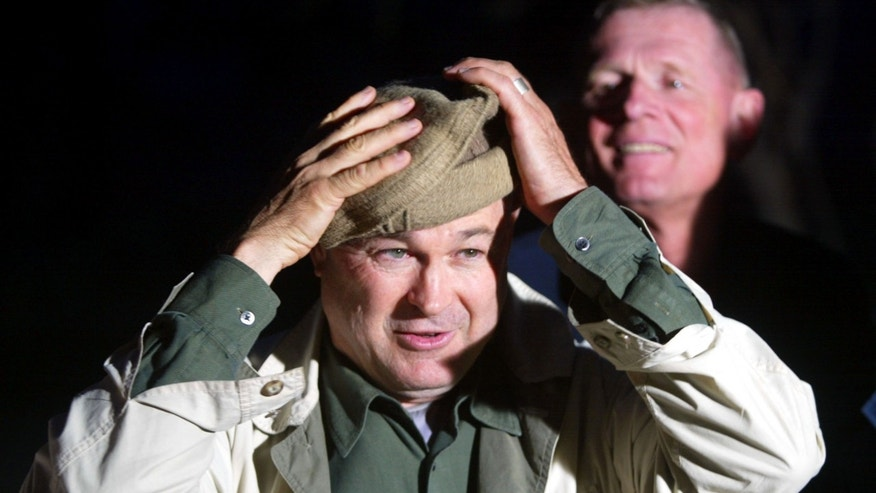 Rep. Dana Rohrabacher (R-California) fixes his Pakhul as Rep. Edwad Schrock (R-Virginia) looks on as they visit April 3, 2002 the Bagram Air Base in Afghanistan.