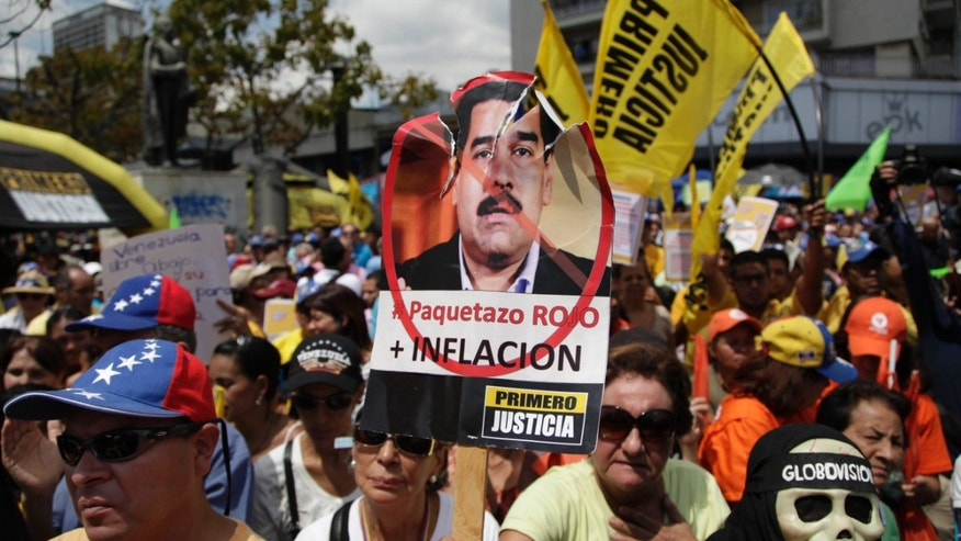 "A protester holds up a picture of Venezuela's Vice President Nicolas Maduro that reads in Spanish ""Big red package, plus inflation"" during an opposition demonstration against of the devaluation of the currency in Caracas, Venezuela, Saturday, Feb. 23, 2013.  (AP Photo/Ariana Cubillos)"