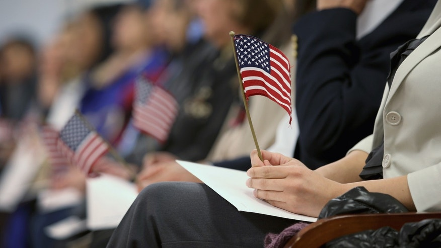 NEWARK, NJ - JANUARY 28:  Immigrants hold flags while waiting for a naturalization ceremony to become U.S. citizens at the district office of U.S. Citizenship and Immigration Services (USCIS) on January 28, 2013 in Newark, New Jersey. Some 38,000 immigrants became U.S. citizens at the Newark office alone in 2012.  (Photo by John Moore/Getty Images)