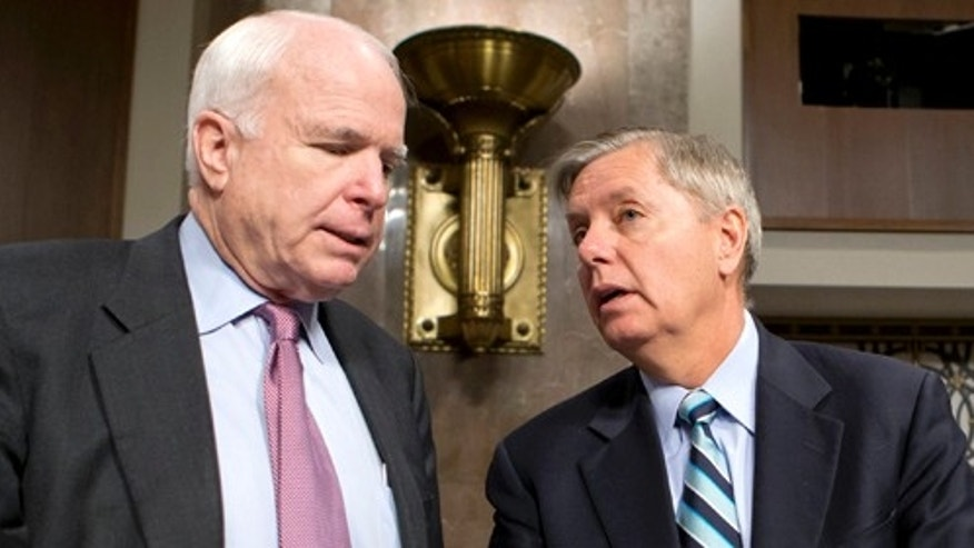 FILE - In this Feb. 14, 2013 file photo, Sen. John McCain, R-Ariz., left, and Sen. Lindsey Graham, R-S.C. confer on Capitol Hill in Washington. McCain, Sen. Lindsey Graham, R-S.C., Sen. and Jeff Flake, R-Ariz. met with key House conservatives this week to promote legislation to overhaul the nation's immigration laws and provide a pathway to citizenship for an estimated 11 million illegal immigrants, McCainâs communications director said Friday. (AP Photo/J. Scott Applewhite, File)