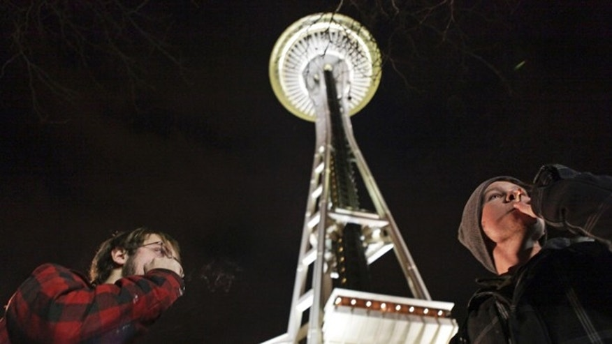 FILE: Dec. 6, 2012: People light up near the Space Needle after the law legalizing the recreational use of marijuana went into effect in Seattle, Washington.