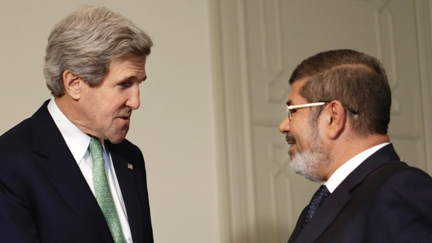 FILE: March 3, 2013: Secretary of State John Kerry, left, shakes hands with Egyptian President Mohamed Morsi at the Presidential Palace in Cairo, Egypt.