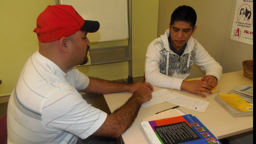 Mexican immigrant Gabriel Moreno, right, tutors a newcomer and compatriot in English. Moreno is part of a growing network of Latinos who have been in Baltimore for several years and are helping recent arrivals adjust.
