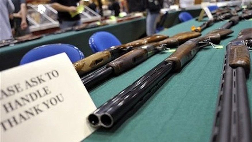 File: June 19, 2010: Assorted shotguns are displayed on a table at a gun and knife show in White Plains, N.Y.,
