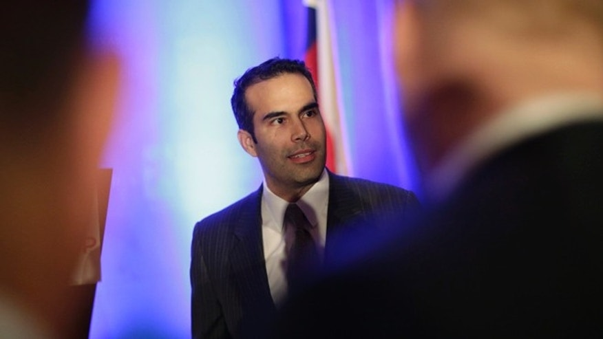Feb. 26, 2013: In this file photo, George P. Bush, left, talks to businessmen prior to making the opening statements at the Texas Business Leadership Council in Austin, Texas.