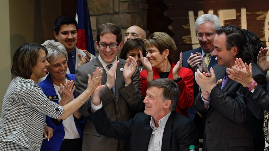 March 21, 2013: Colorado Gov. John Hickenlooper, center, exchanges high-fives with members of the State Legislature after he signs the Civil Unions Act into law at the Colorado History Museum in Denver, Colo.