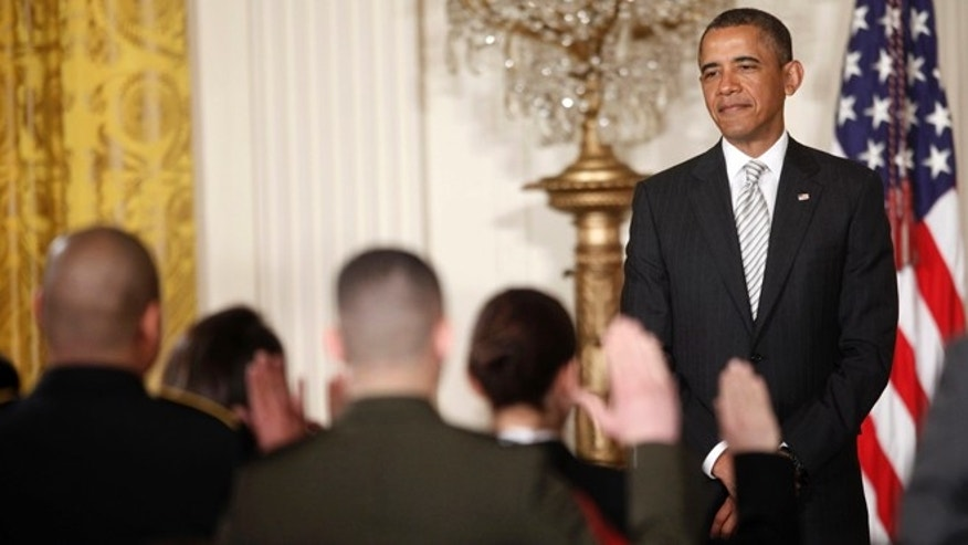 President Barack Obama, watches as the Oath of Allegiance is administered at a naturalization ceremony for active duty service members and civilians, Monday, March 25, 2013, in the East Room of the White House in Washington.