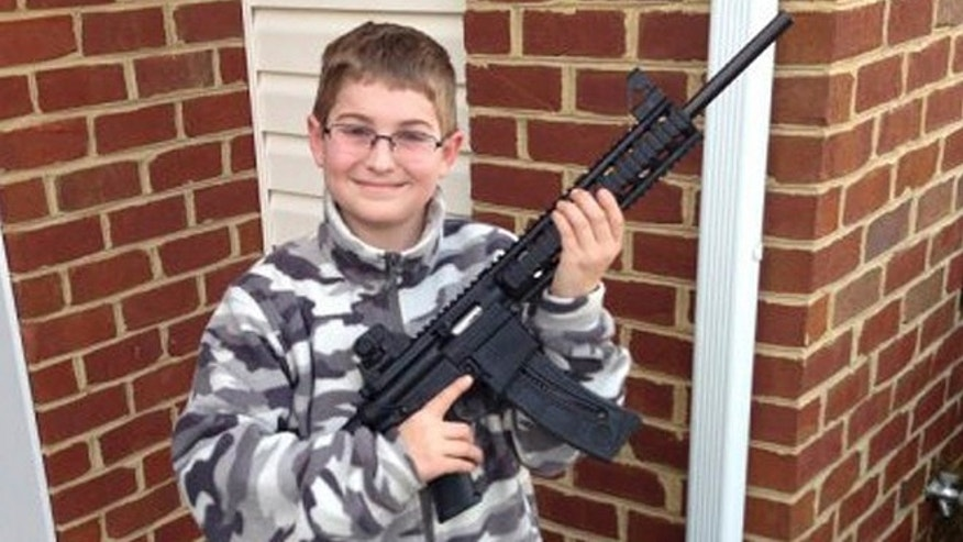 This undated photo provided by Shawn Moore shows his son Josh, 10, holding a rifle his father gave him for his 11th birthday, at their home in Carneys Point, N.J.