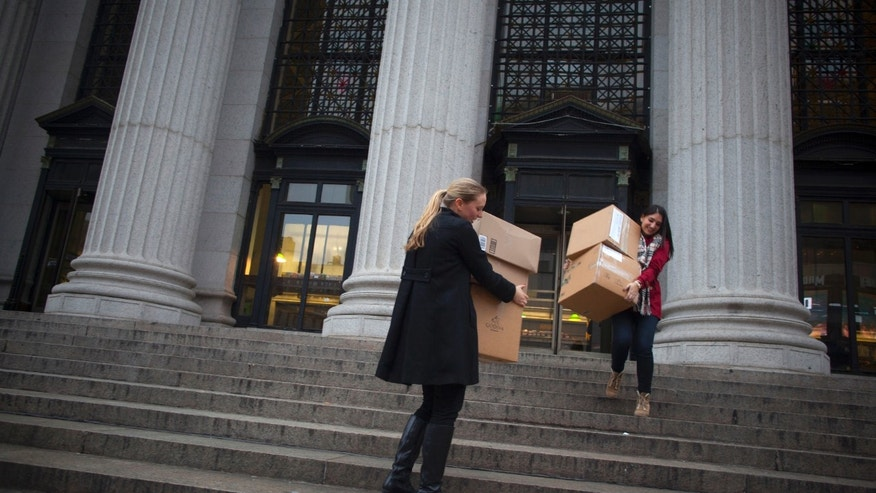 FILE: December 17, 2012: Women carry packages into the James A. Farley Post Office Building in New York City.