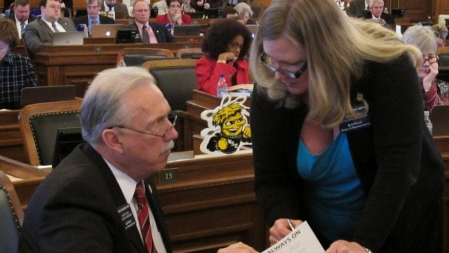 March 19, 2013: Kansas state Rep. Tom Burroughs, left, consults with Rep. Julie Menghini, of Pittsburg, during the House's debate on anti-abortion legislation at the Statehouse in Topeka, Kan.