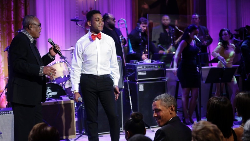 April 9, 2013: President Barack Obama, center seated, looks over towards his daughter Sasha, as singers Sam Moore, left, and Joshua Ledet, right, perform on stage during the In Performance at the White House in the East Room of the White House in Washington, a program for a celebration of Memphis Soul Music.