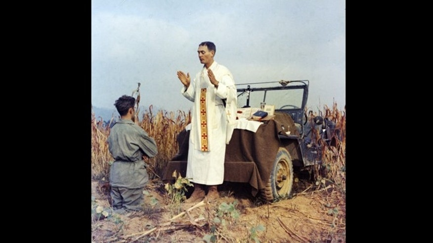 In this photo provided by Col. Raymond A. Skeehan, Father Emil Kapaun celebrates Mass using the hood of his jeep as an altar, as his assistant, Patrick J. Schuler, kneels in prayer in Korea on Oct. 7, 1950, less than a month before Kapaun was taken prisoner. Kapaun died in a prisoner of war camp on May 23, 1951, his body wracked by pneumonia and dysentery.
