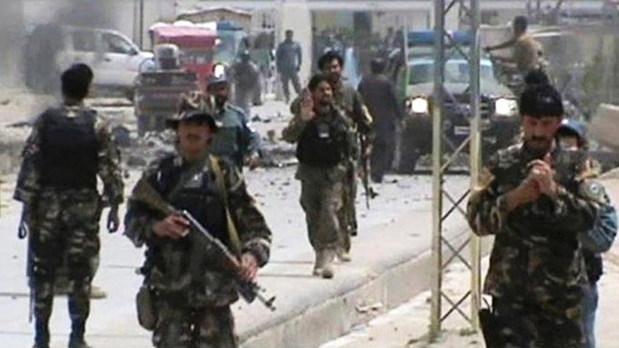 April 6, 2013: In this file image made from AP video, Afghan National Army soldier rush to the scene moments after a car bomb exploded in front the PRT, Provincial Reconstruction Team, in Qalat, Zabul province, southern Afghanistan.