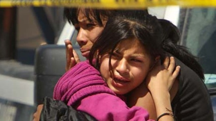 Family members cry in front of a car in which two men lay dead on March 22, 2010 in Juarez, Mexico.