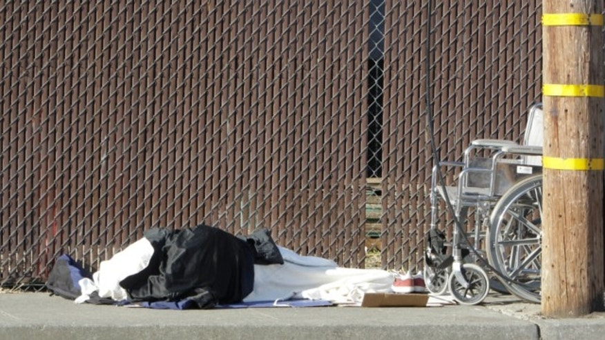 April 23, 2013: A homeless person sleeps on a sidewalk in Sacramento, Calif.