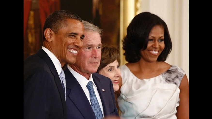 U.S. President Barack Obama (L) poses alongside former U.S. President George W. Bush, former first lady Laura Bush and first lady Michelle Obama (R) after the Bush's official White House portraits were unveiled during a ceremony in the East Room of the White House in Washington May 31, 2012.