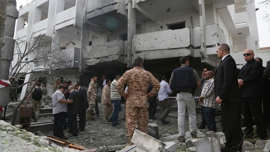 April 23, 2013: Security officers and officials inspect the site of a car bomb that targeted the French embassy wounding two French guards and causing extensive material damage in Tripoli, Libya.