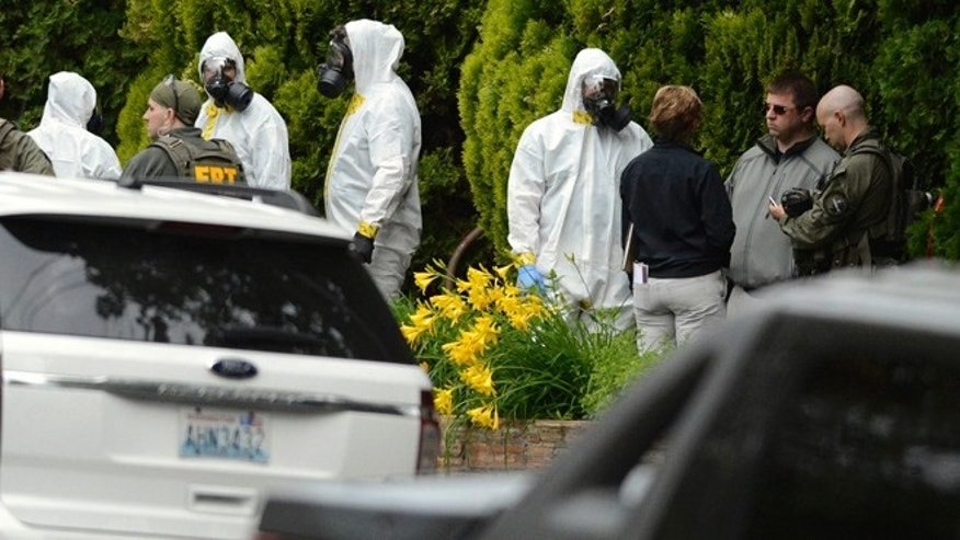 May 18, 2013: During the execution of a search warrant, members of the Joint Federal Haz-Mat Team, FBI, and local law enforcement gather in front of the Osmun Apartments near the intersection of First Avenue and Oak Street in Browne's Addition in Spokane, Wash.
