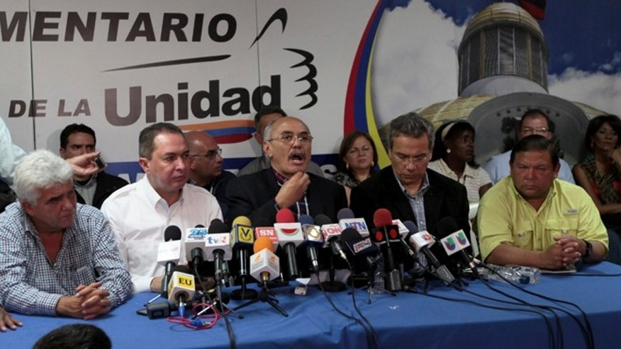 Opposition lawmaker Ismael Garcia, center, speaks during a news conference in Caracas, Venezuela, Monday, May 20, 2013.