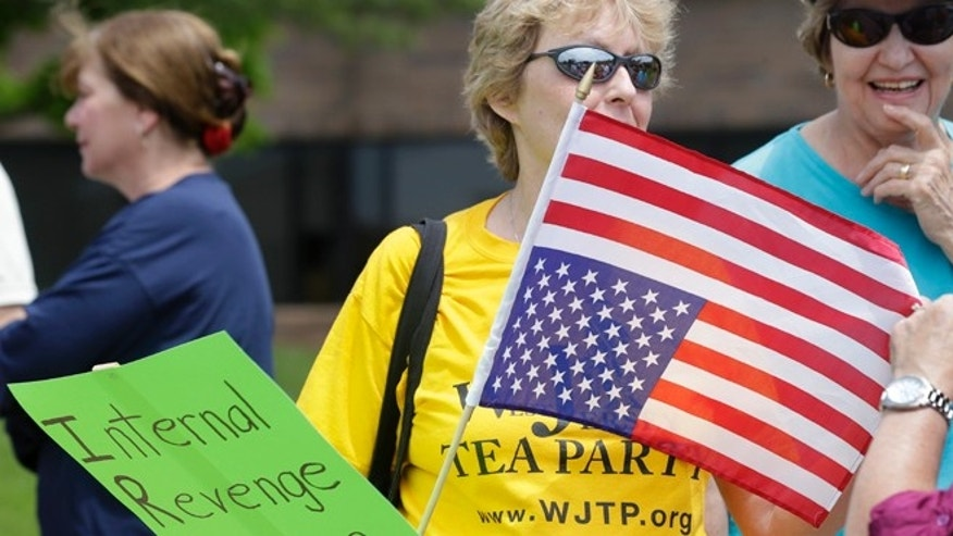 May 21, 2013: A woman holds an upside-down flag during a tea party rally protesting extra IRS scrutiny of their groups in Cherry Hill, N.J.