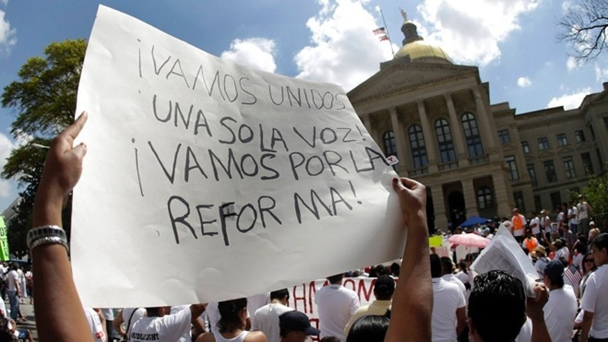 April 10, 2013: A protester for immigration reform holds a sign during a rally at the Georgia State Capitol in Atlanta.
