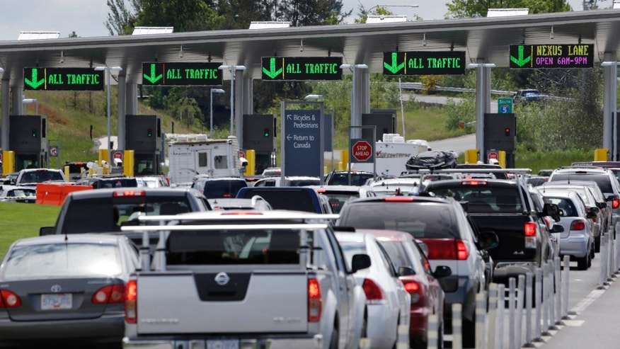 Cars from Canada line up to cross into the U.S. in Blaine, Wash.