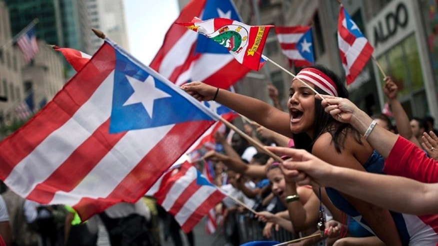 NEW YORK, NEW YORK - JUNE 10: Revelers gather along Fifth Avenue during the Puerto Rican Day Parade on June 10, 2012 in New York City. The Puerto Rican Day Parade draws hundreds of thousands and was first celebrated in New York City in 1958. (Photo by Allison Joyce/Getty Images)