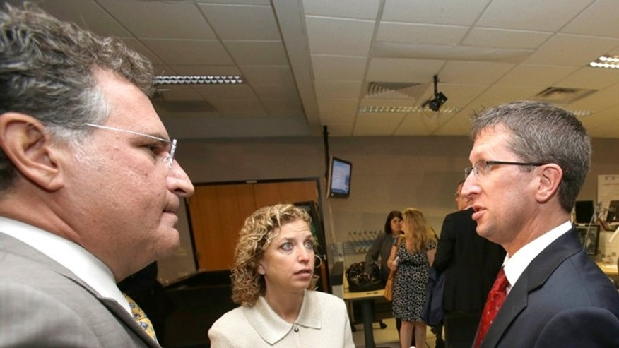 FILE: May 31, 2013: Rep Joe Garcia, D-Fla., with Rick Knabb, National Hurricane Center director, and Rep. Debbie Wasserman Schultz, D-Fla., at the National Hurricane Center in Miami, Fla.