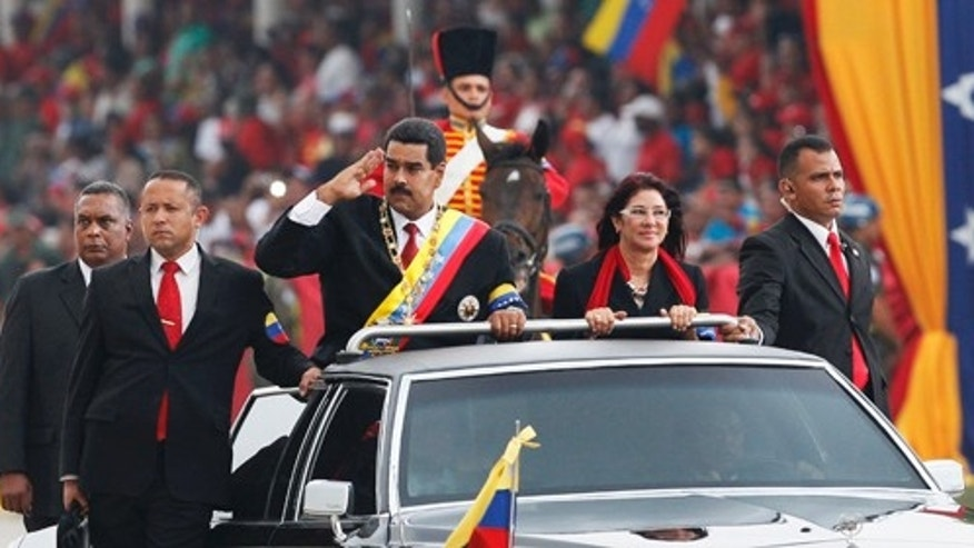 "Venezuela's President Nicolas Maduro salutes from a vehicle, next to his companion Cilia Flores, during a military ceremony recognizing him as Commander-in-chief along the Paseo de Los Proceres, or ""Promenade of the Forefathers"" in Caracas, Venezuela, Friday, April, 19, 2013.  Maduro, who has the support of the Chavista bases, needs all the momentum he can muster to consolidate control of a country struggling with shortages of food and medicines; chronic power outages; one of the world's highest homicide and kidnapping rates. (AP Photo/Ariana Cubillos)"