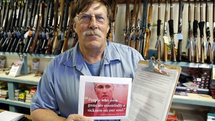 May 24, 2013: Paradise Firearms owner Paul Paradis holds a flyer depicting Colorado's State Senate President, Democrat John Morse, together with a petition to recall him, right, at his gun shop in Colorado Springs, Colo.