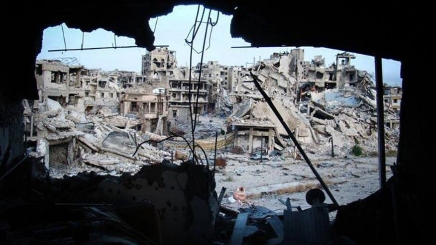 June 5, 2013: In this citizen journalism image provided by Lens Young Homsi, which has been authenticated based on its contents and other AP reporting, shows damaged buildings are seen in the Jouret al-Chiyah neighborhood, Homs province, central Syria.