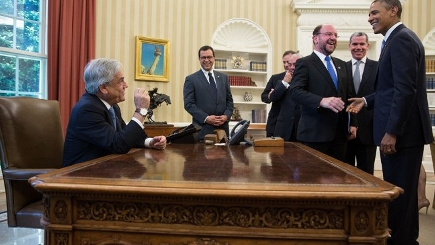 President Barack Obama jokes with members of the Chilean delegation as President Sebastián Piñera of Chile sits at the Resolute Desk following a bilateral meeting in the Oval Office, June 4, 2013.