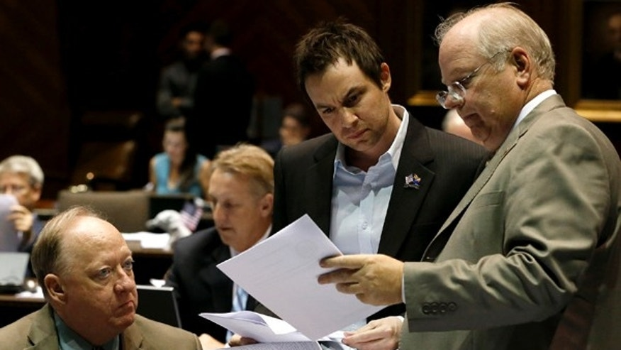 June 12, 2013: House Speaker Rep. Andy Tobin, R-Paulden, right, confers with Speak Pro-Tempore Rep. J.D. Mesnard, R-Chandler, and Majority Whip Rep. Rick Gray, R-Sun City, left, in a special session budget battle for Medicaid funding in Phoenix.