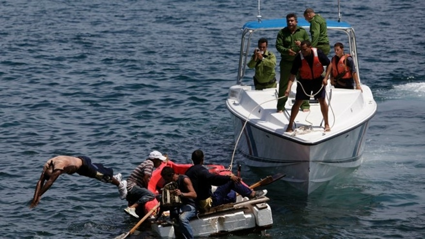 In this June 4, 2009 file photo, Cuban coast guards, right, stop seven men trying to migrate illegally to the U.S. on a foam raft near Havana's Malecon.  No one was arrested, according to police.