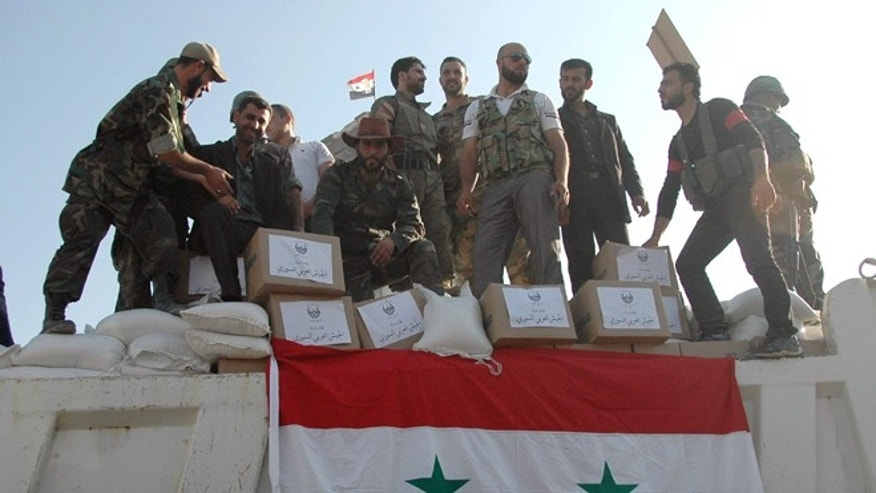 In this photo released on June 5, 2013 by the Syrian official news agency SANA, Syrian soldiers loyal to President Bashar Assad stand on a truck full of aid supplies in Qusair, Syria.