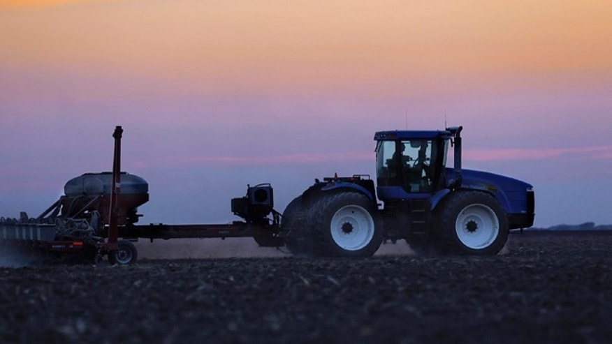 In this Saturday, June 8, 2013 photo, a central Illinois farmer continues planting corn seed into the evening in Farmingdale, Ill.