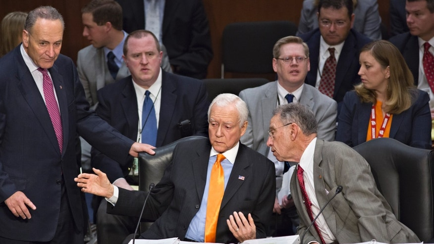 FILE  In this May 9, 2013, file photo Sen. Orrin G. Hatch, R-Utah, confers with Sen. Chuck Grassley, R-Iowa, right, and Sen. Chuck Schumer, D-N.Y., left, as the Senate Judiciary Committee meets to address immigration reform on Capitol Hill in Washington. More than any other group, the high-tech industry got big wins in the immigration bill  approved last week. It amounted to a bonanza for the industry, granting unlimited green cards to foreigners with certain advanced U.S. degrees, and greatly boosting visas for highly skilled foreign workers. And thanks to Hatch's intervention, the industry succeeded in greatly curtailing controls sought by Sen. Dick Durbin, D-Ill., not shown, who aimed to protect U.S. workers.  (AP Photo/J. Scott Applewhite, File)