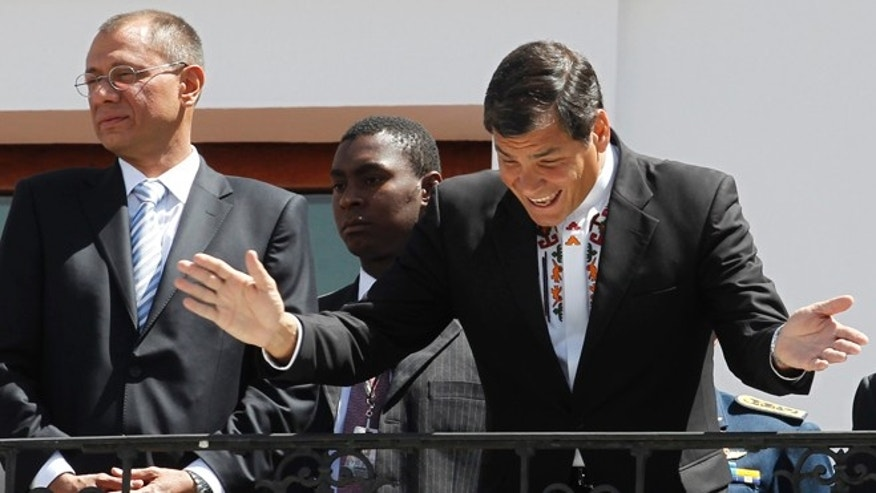 June 24, 2013: Ecuador President Rafael Correa, right, greets passersby from the balcony of the presidential palace.