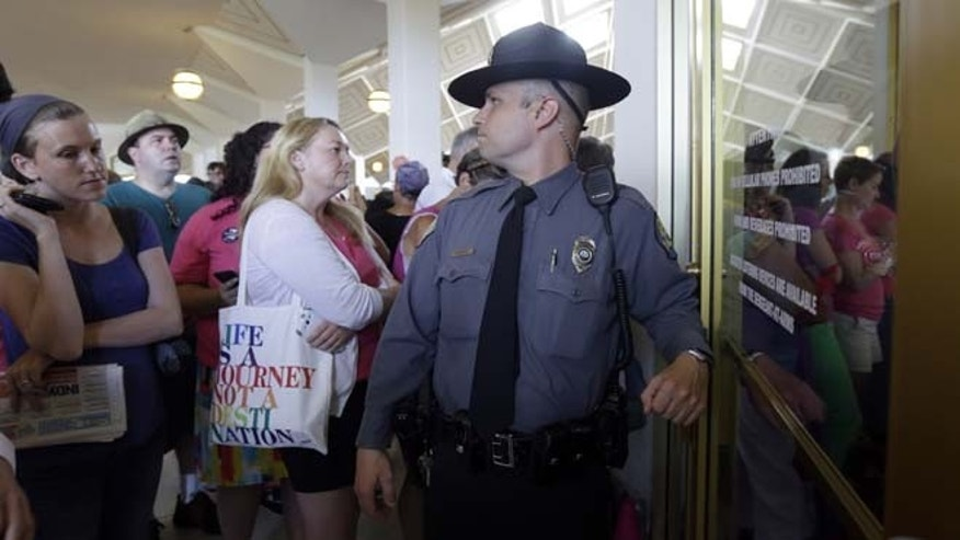 July 3, 2013: Capitol police stand guard at an entrance to the Senate gallery as people gather at the state legislature while Senate Republicans gave their final approval to legislation requiring additional rules surrounding abortions in North Carolina, even as hundreds of protesters against the bill watched from the gallery in Raleigh, N.C. The Senate voted 29-12 Wednesday for the measure that would direct regulators to change abortion clinic rules so they're similar to those for ambulatory surgery centers.