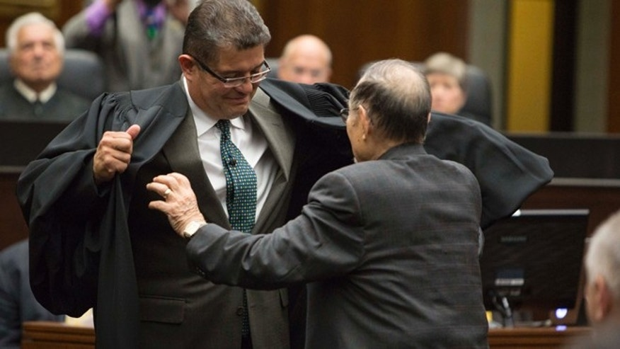 Judge Ruben Castillo is helped with his new robe by his father, Ruben Castillo Sr. after being sworn in as chief judge of the U.S. District Court Northern District of Illinois in Chicago, Tuesday, July 2, 2013. Castillo is the first Hispanic to become chief judge of the district. He had been a U.S. district court judge for 19 years. (AP Photo/Scott Eisen)