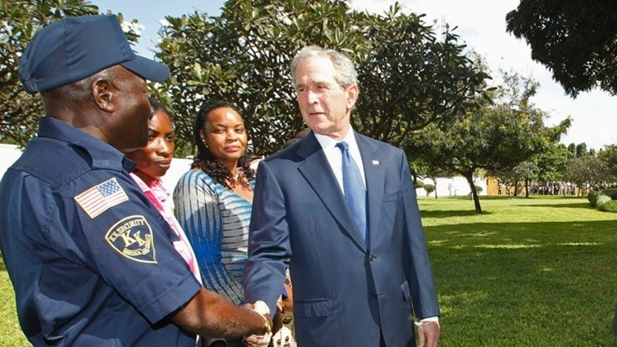 FILE July 2, 2013: Former President George W. Bush greet relatives of those killed in the 1998 U.S. Embassy bombing in Dar es Salaam, in Tanzania.