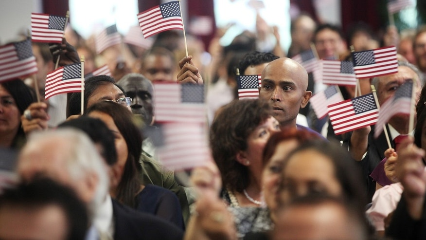 NEW YORK, NY - JULY 02:  People wave American flags at a naturalization ceremony in downtown Manhattan on July 2, 2013 in New York City. U.S. Citizenship and Immigration Services (USCIS) conducted three naturalization ceremonies for 450 people today in Manhattan ahead of the July 4th holiday.  (Photo by Mario Tama/Getty Images)