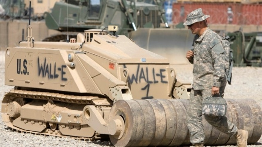 "March 10, 2010: A U.S. Army's soldier walks past a de-mining robot named after the computer animated character ""Wall-E"" at Camp Leatherneck in Helmand province, southern Afghanistan."